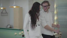 Blonder bärtiger Mann des Porträts und seine Freundin, die nahe dem Billardtisch spricht Überzeugter Mann im weißen Hemd erklärt  stock footage
