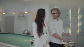 Blonder bärtiger Mann und seine Freundin, die nahe dem Billardtisch spricht ?berzeugter Mann im wei?en Hemd erkl?rt der Frau stock video