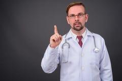 Blonder bärtiger Manndoktor mit dem Spitzbart gegen grauen Hintergrund lizenzfreie stockbilder