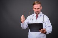 Blonder bärtiger Manndoktor mit dem Spitzbart gegen grauen Hintergrund lizenzfreies stockfoto