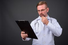 Blonder bärtiger Manndoktor mit dem Spitzbart gegen grauen Hintergrund stockbild