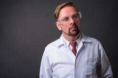 Blonder bärtiger Manndoktor mit dem Spitzbart gegen grauen Hintergrund stockfotos