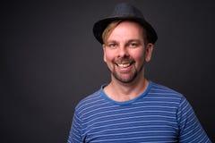 Blonder bärtiger touristischer Mann mit dem Spitzbart gegen grauen Hintergrund lizenzfreies stockfoto