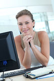 Blonder Büroangestellter, der am Schreibtisch sitzt Stockfotos