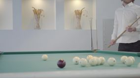 Blonder b?rtiger Mann, der Pool, Billard im hellen Raum spielt ?berzeugter Spieler schl?gt den Ball mit einem Stichwort Amerikani stock video footage