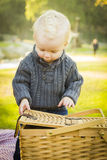 Blonder Baby-Öffnungs-Picknick-Korb draußen am Park Stockfoto