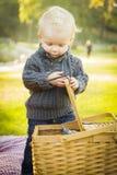 Blonder Baby-Öffnungs-Picknick-Korb draußen am Park Stockfotografie
