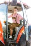 Blonder bayerischer Mann, der auf Traktor sitzt Lizenzfreie Stockfotografie