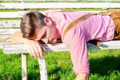 Blonder bayerischer Mann, der draußen auf einer Bank schläft Stockfotos