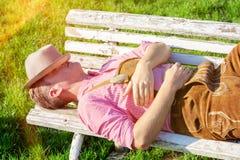 Blonder bayerischer Mann, der draußen auf einer Bank schläft Stockbild