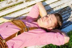 Blonder bayerischer Mann, der draußen auf einer Bank schläft Lizenzfreie Stockfotos