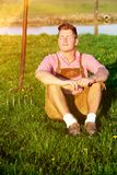 Blonder bayerischer Mann, der im Gras sitzt Lizenzfreie Stockfotografie
