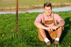 Blonder bayerischer Mann, der im Gras sitzt Stockfotografie