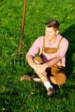 Blonder bayerischer Mann, der im Gras sitzt Stockfotos