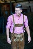 Blonder bayerischer Mann, der an der Scheune steht Lizenzfreies Stockfoto