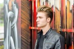 Blonder behaarter junger Mann, der gegen Graffiti steht Stockbilder