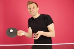 Blonder behaarter Mann, der Tischtennis spielt Stockfotografie