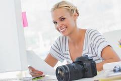Blonder Bildeditor, der ein Kontaktblatt hält Lizenzfreie Stockbilder