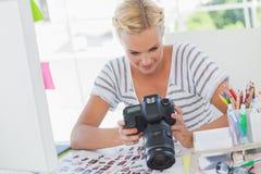 Blonder Bildeditor, der eine Digitalkamera betrachtet Stockfotografie
