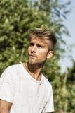 Blonder, blauäugiger junger Mann im Freien in der Sonne Stockbild
