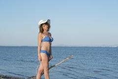 Blonder blauer Bikini der Frauenabnutzung und weißer Hut, die in dem Meer steht Stockfoto