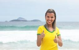 Blonder brasilianischer Sportfan, der Daumen am Strand zeigt Lizenzfreie Stockbilder