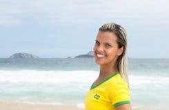 Blonder brasilianischer Sportfan am Strand ist glücklich Stockbild