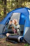 Blonder Camper, der durch Ferngläser schaut Lizenzfreie Stockbilder