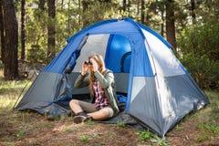 Blonder Camper, der durch Ferngläser schaut Stockfotos
