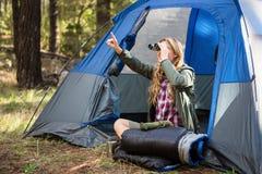Blonder Camper, der durch Ferngläser schaut Lizenzfreie Stockfotos