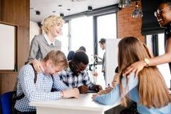 Blonder Chef, der ihre Arbeitskräfte sich lustig macht über Büroangestellter mit dem angemessenen Haar Lizenzfreie Stockbilder