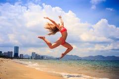 blonder dünner Turner im Bikini im Sprung über Strand gegen Himmel Lizenzfreie Stockfotografie