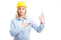 Blonder Dameningenieur, der Eid mit der Hand oben schwört Lizenzfreie Stockfotos