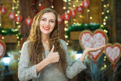 Blonder darstellender Daumen oben und Showwaren an Valentinsgruß ` s Tag Stockbild