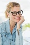 Blonder Designer, der die Kamera mit einem Lächeln betrachtet Stockfotos