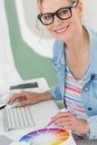 Blonder Designer, der ein Farbrad lächelt an der Kamera verwendet Lizenzfreie Stockbilder