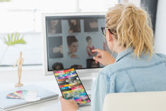 Blonder Designer, der eine Farbtafel an ihrem Schreibtisch verwendet Lizenzfreie Stockfotos