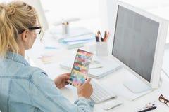 Blonder Designer, der Farbmuster an ihrem Schreibtisch hält Stockfotos