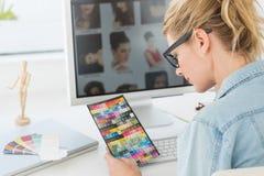 Blonder Designer, der Farbtafel auf ihren Schreibtisch betrachtet Stockbilder