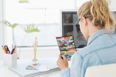 Blonder Designer, der Farbtafel auf Schreibtisch betrachtet Lizenzfreie Stockbilder