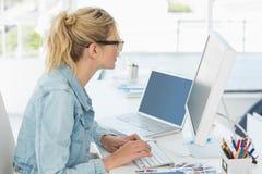 Blonder Designer, der an ihrem Schreibtisch arbeitet Lizenzfreie Stockfotos