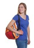 Blonder deutscher Student mit der Tasche, die zurück schaut Lizenzfreie Stockbilder