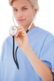 Blonder Doktor, der mit Stethoskop hört Lizenzfreie Stockbilder