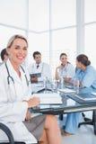 Blonder Doktor, der nahe bei ihrem Ärzteteam sitzt Stockfotografie