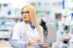 Blonder Doktor, junger Apotheker, der nach verschreibungspflichtigen Medikamenten auf Laptop sucht Apothekenfrau, die moderne Tec Stockbilder