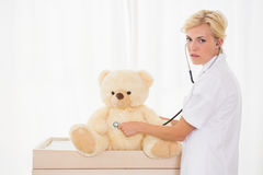 Blonder Doktor mit Bären und Stethoskop Stockfoto