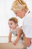 Blonder Doktor mit einem Kind und einem Stethoskop Lizenzfreie Stockbilder