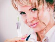 Blonder Doktor mit Spritze Lizenzfreie Stockbilder