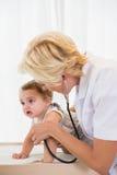 Blonder Doktor mit Stethoskop und Kind Stockbilder