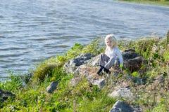 Blonder durchdachter Junge, der in einer Flussbank auf Felsen sitzt Lizenzfreie Stockbilder